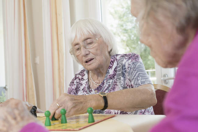 Senior women playing board game in rest home — Stock Photo