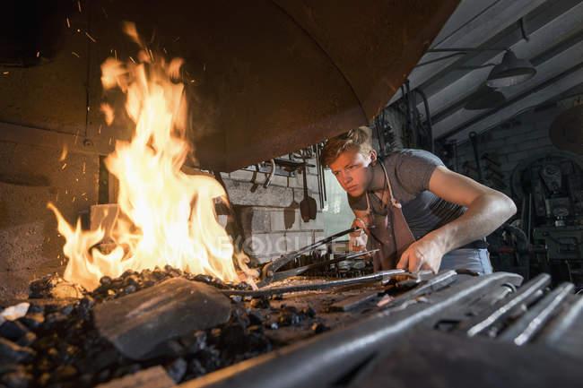 Blacksmith apprentice lightning fire in furnace at workshop — Stock Photo