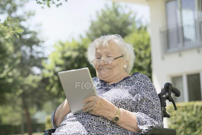Ältere Frau mit digital-Tablette auf Rollstuhl — Stockfoto