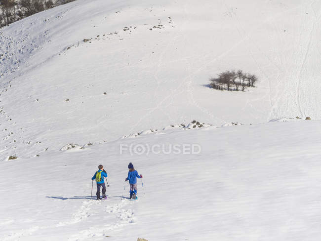Boy and girl with snowshoes walking on snowfield at Anboto mountain — Stock Photo