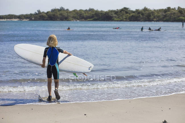 Rear view of girl with surfboard at beach — Stock Photo