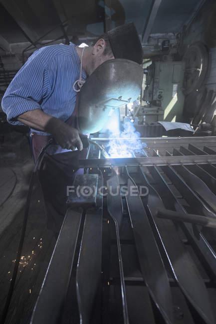 Blacksmith fusing garden gate in workshop — Stock Photo