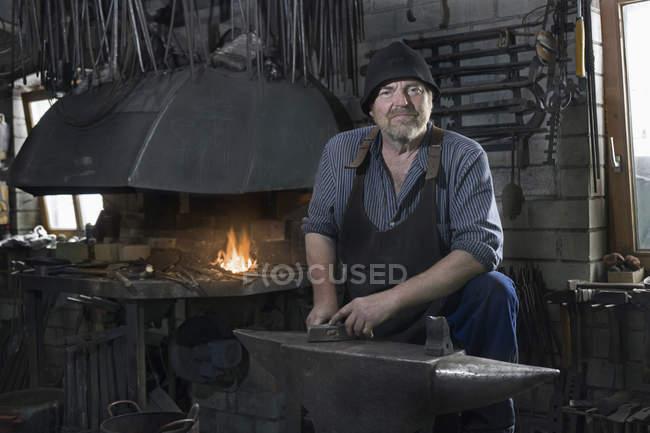 Senior blacksmith in traditional workshop — Stock Photo