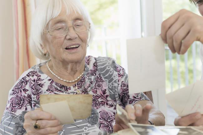 Mulher sênior, vendo fotos com zelador na casa de repouso — Fotografia de Stock