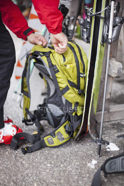 Cropped view of skier fastening backpack — Stock Photo