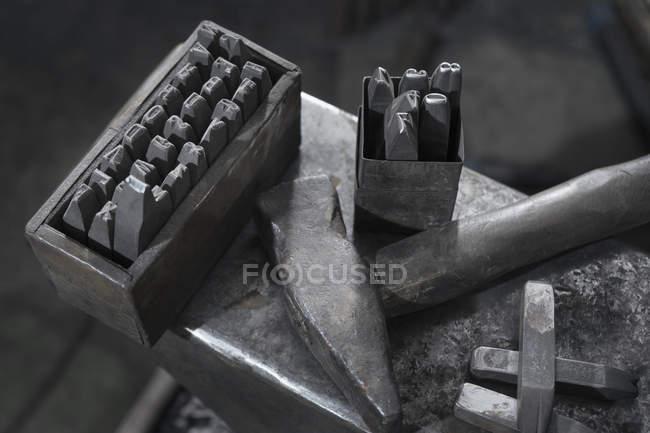 Stanz-Werkzeug und Hammer am Amboss an Schmiede — Stockfoto
