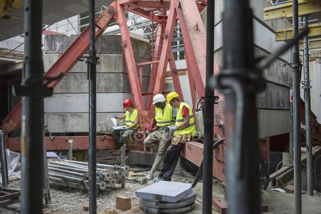 Будівництво працівників із архітектурний план і цифрових таблиці в будівлі сайту — стокове фото