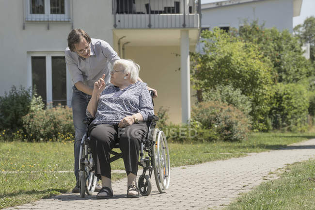 Son walking with disabled mother in wheelchair — Stock Photo