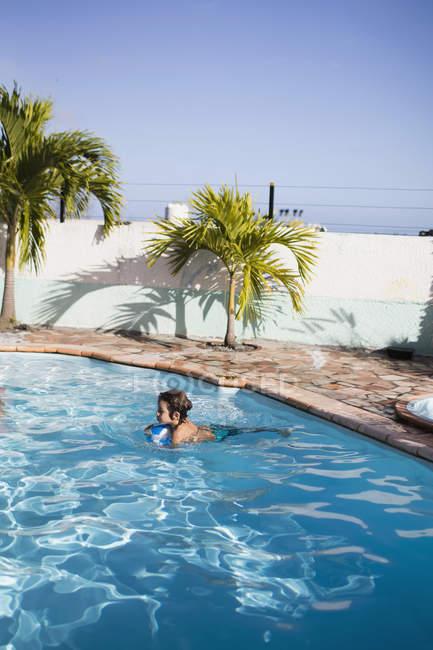Junge mit aufblasbaren Ball im Pool schwimmen — Stockfoto