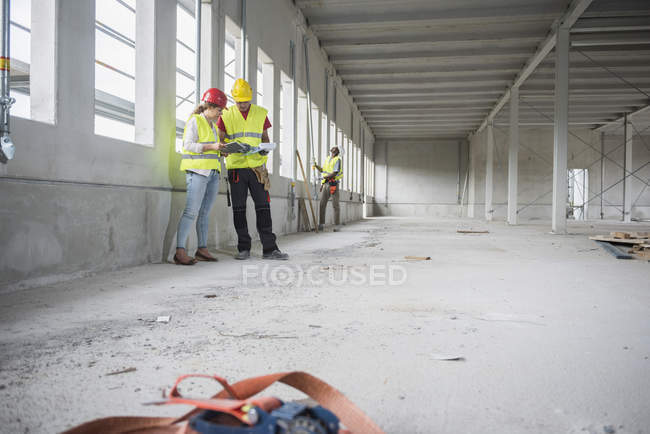 Construction workers reviewing documents at building site — Stock Photo