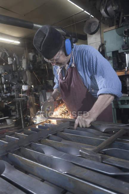 Schmiede Eisen Schneidschiene mit Winkelschleifer in Werkstatt — Stockfoto