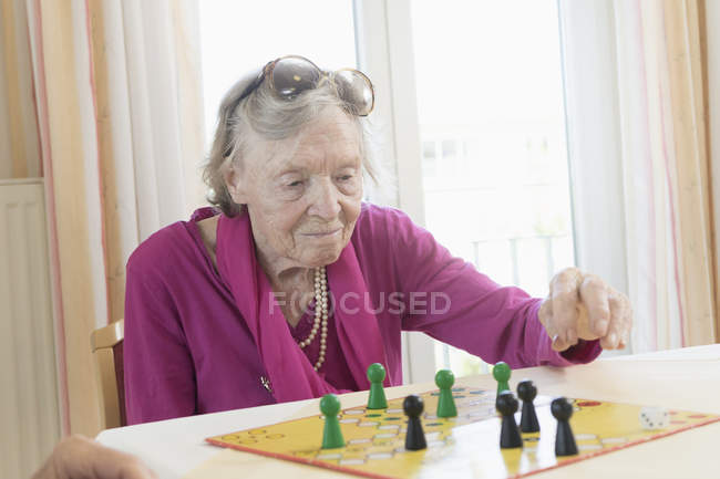 Senior woman playing board game in rest home — Stock Photo