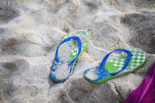 Pair of slippers on beach sand — Stock Photo