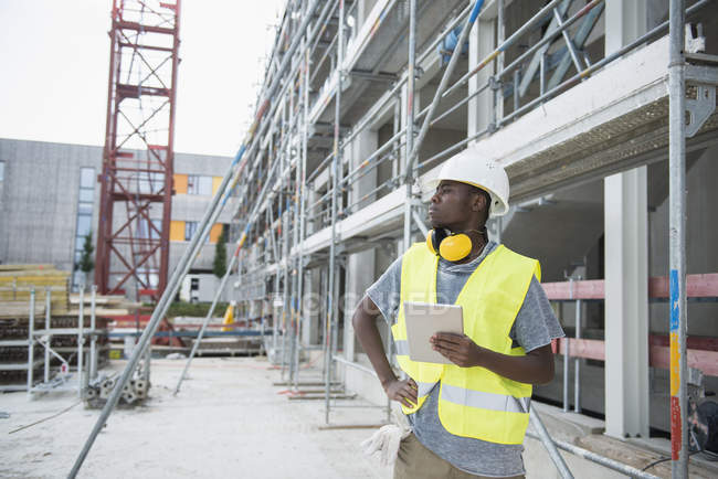 Construction worker holding digital tablet at building site — Stock Photo
