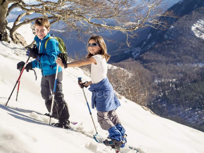 Мальчик и девочка с снегоступы, ходить по snowfield на горе Anboto — стоковое фото