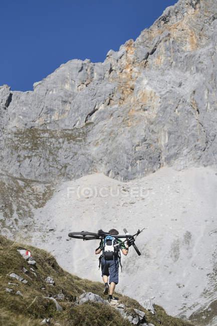 Biciclista de montanha carregando bicicleta nos ombros nas montanhas do Tirol, Áustria — Fotografia de Stock