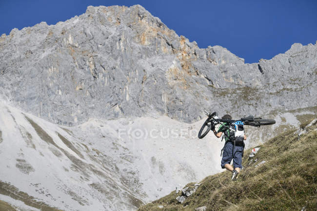 Mountain biker carrying bicycle on shoulders in mountains of Tyrol, Austria — Stock Photo