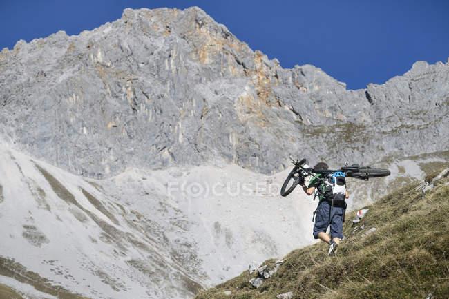 Mountainbiker trägt Fahrrad auf Schultern in Tirols Bergen, Österreich — Stockfoto