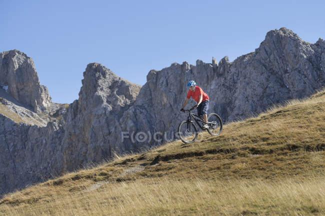 Горный байкер езда вниз склон в альпийских пейзажей, Тироль, Австрия — стоковое фото
