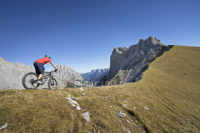 Mountain biker riding down hill in alpine landscape, Tyrol, Austria — Stock Photo