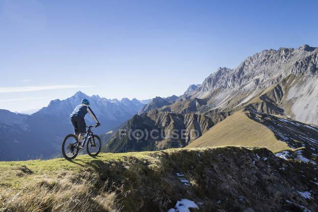 Mountain biker montando em subida na paisagem alpina no Tirol, Áustria — Fotografia de Stock