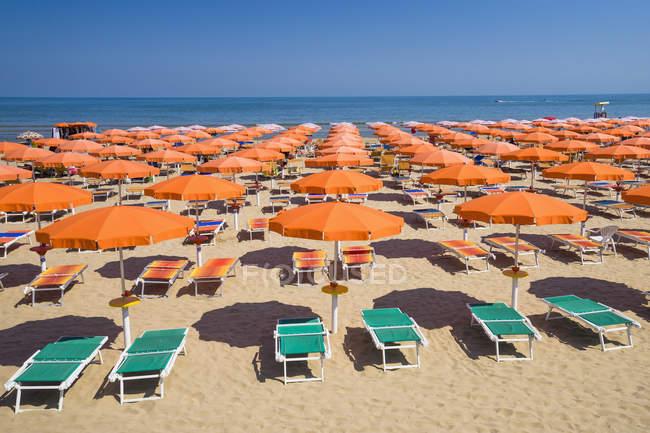 Зонты и стулья на песчаном пляже в Апулии, Италия — стоковое фото