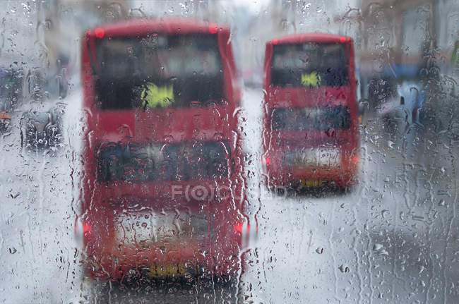 Public buses on road during rainy weather, London, England — Stock Photo