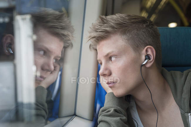 Teen boy listening music on headphones and looking through window in train — Stock Photo