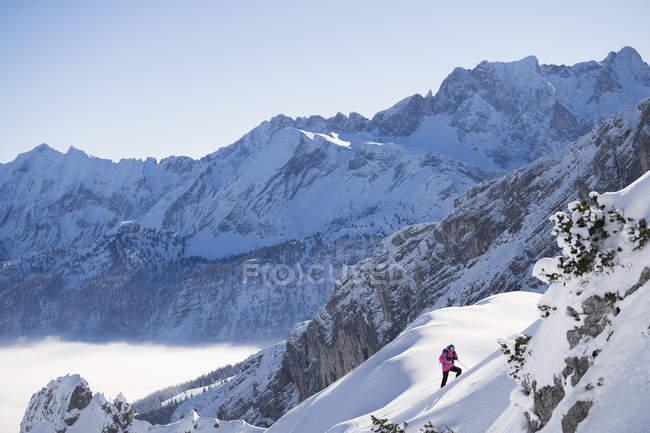 Жінка в рожевий жакет, піднімаючись лижний схил, Баварія, Німеччина, Європа — стокове фото