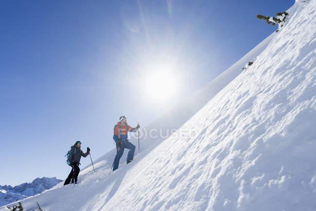 Пара, поднимаясь лыжный склон в верхней Баварии, Германия, Европа — стоковое фото