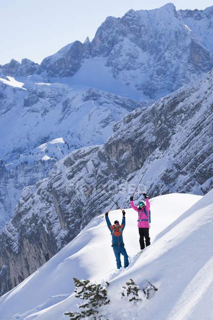 Skiers with raising arms holding ski poles, Bavaria, Germany, Europe — Stock Photo
