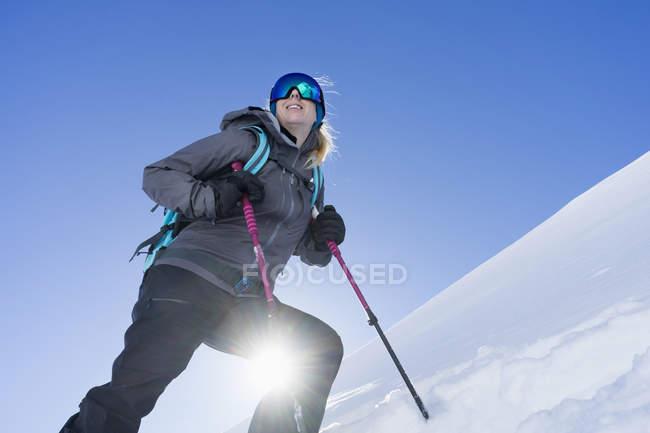 Низкий угол зрения женщины, Катание на лыжах в яркий солнечный свет, Баварии, Германия, Европа — стоковое фото