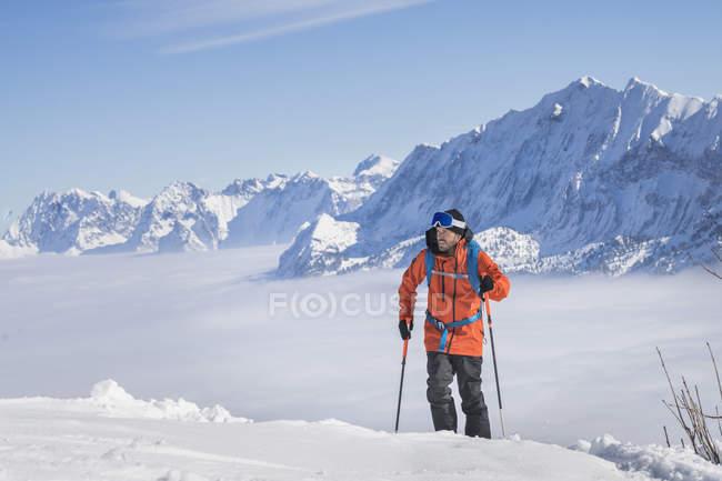 Esquiador masculino escalando a montanha de neve na Alta Baviera, Alemanha, Europa — Fotografia de Stock