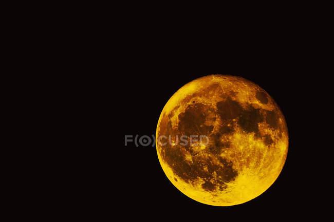 Повний місяць проти чорний небо вночі — стокове фото