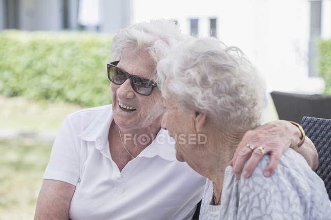 Mulheres idosas sentadas e abraçadas ao ar livre — Fotografia de Stock
