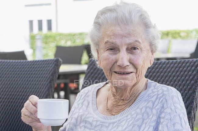 Старшая женщина пьет кофе в саду — стоковое фото