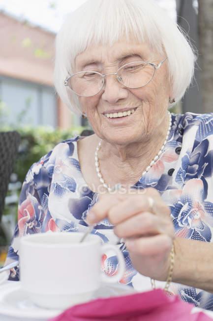 Старшая женщина помешивает чай в саду — стоковое фото