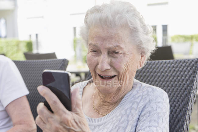 Senior woman smiling and using smartphone in garden — Stock Photo
