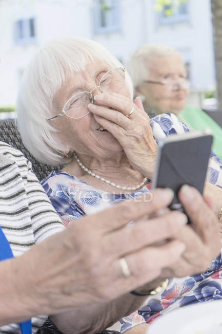 Senior women looking at smartphone and laughing in garden — Stock Photo