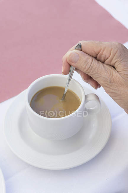 Close-up of hand of senior woman stirring coffee — Stock Photo