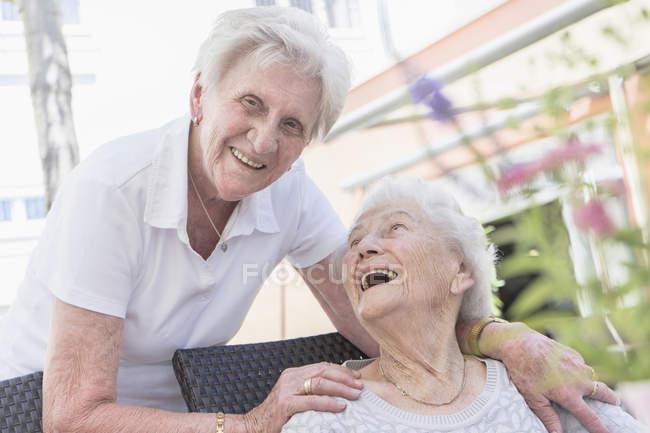 Два старших жінок сміючись в саду в будинку для літніх людей — стокове фото