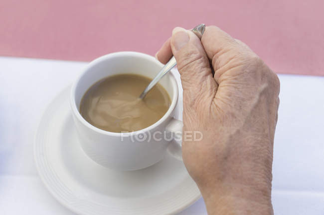 Close-up of hand of senior woman stirring coffee — Stock Photo