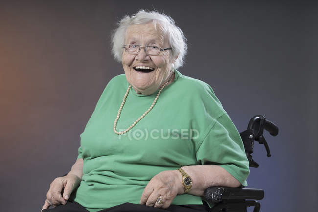 Portrait of senior woman sitting in wheelchair and laughing, studio shot — Stock Photo
