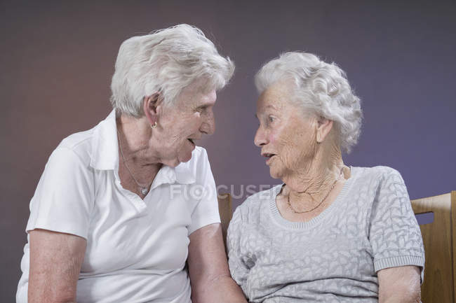 Two senior women talking while sitting in chairs, studio shot — Stock Photo