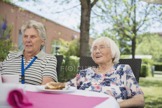 Zwei Seniorinnen frühstücken im Freien im Garten — Stockfoto