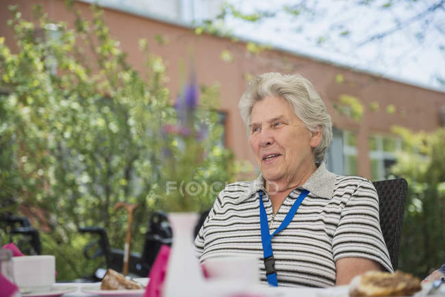 Senior woman resting at breakfast table in garden — Stock Photo
