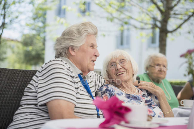Senior women embracing at breakfast table of nursing home — Stock Photo