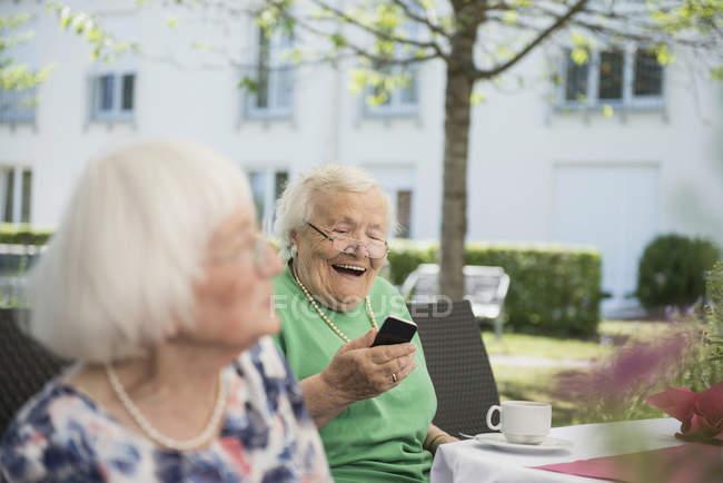 Старші жінки сміятися і дивлячись на смартфон в саду — стокове фото