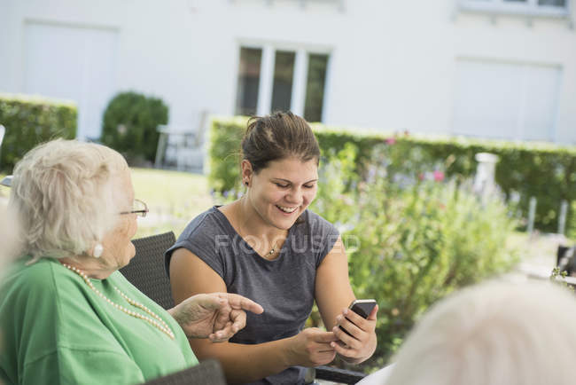 Grandmother and granddaughter discussing over smartphone on garden — Stock Photo