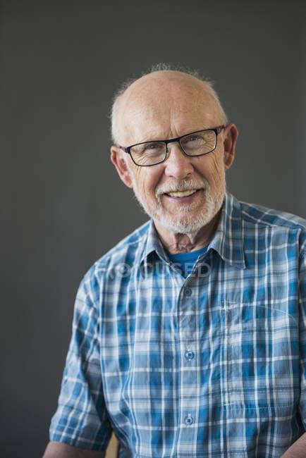 Retrato de homem sênior, sorrindo e olhando na câmera, studio shot — Fotografia de Stock
